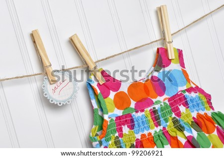 Vibrant Polka Dot Baby Dress on a Clothesline with Handwritten Sale Sign.
