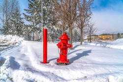 Vibrant red fire hydrant and pole against nature landcsape of snow in winter