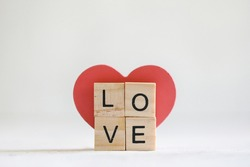 Vibrant red wooden love heart on display with small letter tiles spelling the word LOVE. White background with copy space.