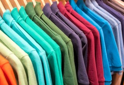 Vibrant shirts on hangs for sale in shop. Multicolored polo on wooden hanger. Summer fashion in department store. Unisex apparel for warm weather. Sale in shopping mall. Color gradient t-shirts