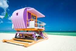 Vibrant sunny view of lifeguard tower painted pastel colors under bright blue sky on South Beach, Miami, Florida