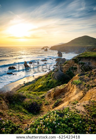 Vibrant Sunset over Peaceful Ocean Waves and Rocks #625423418