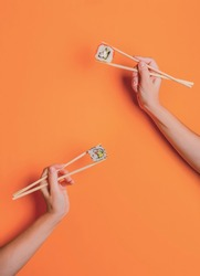 Vibrant sushi set, creative idea concept. Holding Sushi in chopsticks, in hand. Traditional Japanese cuisine concept. Sprinkled with sesame seeds. Over bright color background. Copy space banner.