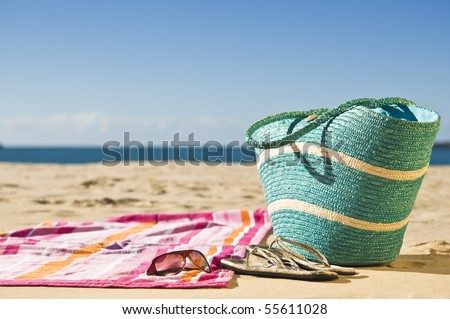 Vibrant towel, beach bag and accessories spread out on the sand.