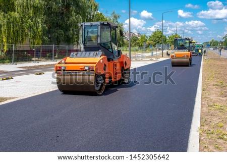 Vibratory asphalt roller compactor on site, compacting new asphalt pavement in urban modern city  Foto stock ©