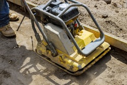 Vibratory plate compactor tool at under construction compacting sand at sidewalk