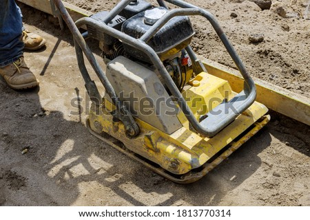 Photo of  Vibratory plate compactor tool at under construction compacting sand at sidewalk