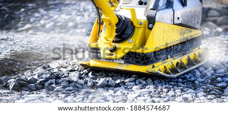 Vibratory plate heavy machine compactor for construction compacting or beating sand at sidewalk. Wide banner or panorama photo. Foto stock ©