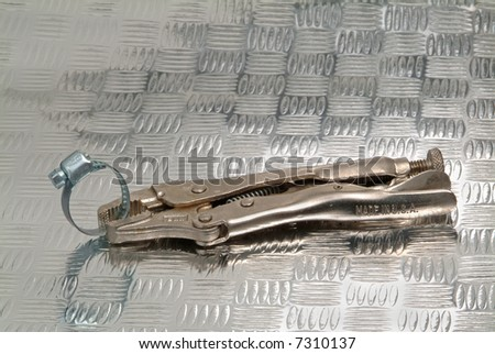 Vice grip pliers on industrial metal background