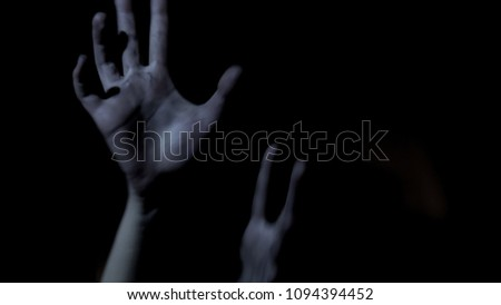 Victim hands stretching out in darkness, begging for help, scary thriller #1094394452