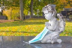 Victim of Coronavirus Covid 19 conceptual photo with sculpture of a little angel holding a protective medical mask on a tomb in cemetery. Selective focus