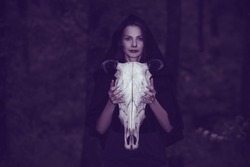 Victim with skull of the animal instead of head. Photo stylized as shooting on an old camera, with noise and imperfection of the image. Woman in forest with skull of cow occupies Occult calls to demon
