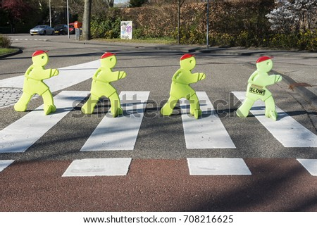 Victor dolls portrayed as beatles on zebra road for theme safety