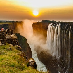 Victoria falls sunset with orange sun in the sky and tourist in view point