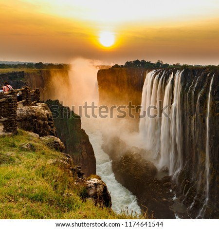 Victoria falls sunset with orange sun in the sky and tourist in view point #1174641544