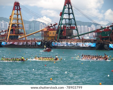 VICTORIA HARBOUR, HONG KONG - JULY 24: Unidentified participants paddle their boats during a dragon boat race on July 24, 2010 in Victoria Harbour, Hong Kong