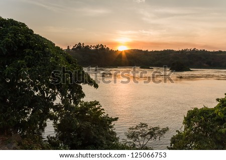 Victoria Nile River at sunset with bright Sun reflecting in water against evening glow background. Jinja, Uganda, Eastern Africa.