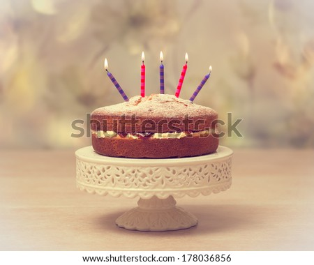 Victoria sponge Birthday cake with lit candles - antique vintage tone effect added