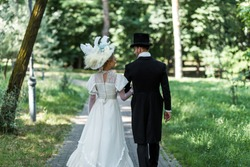 victorian man and woman in hats walking outside near green trees