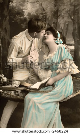 Victorian romance - couple in love on swing - circa 1916 hand-tinted photograph - stock photo