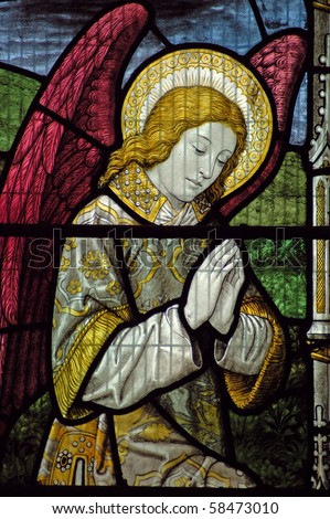Victorian stained glass window depicting an angel praying. An historic window over 100 years old on public display in the church of St Mary Magdalene and St Denys in Midhurst, West Sussex