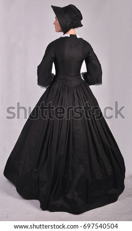 Victorian woman back view wearing a bonnet looking to the left side with plain background #697540504