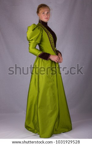 Victorian woman full length plain background green dress right side #1031929528