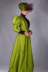 Victorian woman full length plain background green dress wearing hat