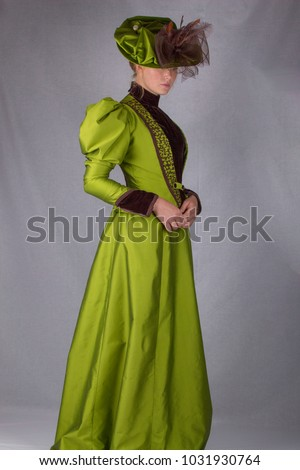 Victorian woman full length plain background green dress wearing hat #1031930764