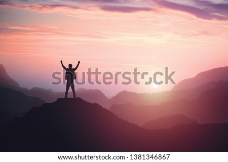 Victorious male person standing on mountain top with arms raised. Winning and success. Achievement and accomplishment in life. Toned image. Сток-фото ©