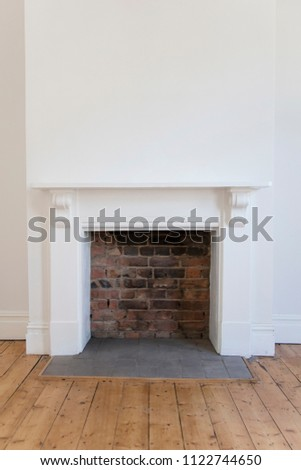 Victoriran wooden fireplace surround with white walls and wooden floor