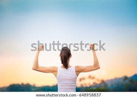 Victory and success! Strong and confident woman flexing.