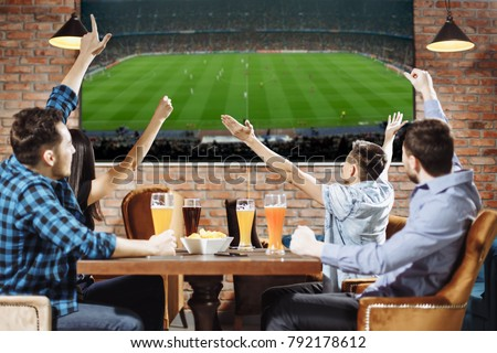 Victory! Group of young beautiful friends watching TV and cheering for their team while resting in pub.