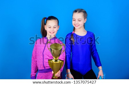 victory of teen girls. Acrobatics and gymnastics. Little girls hold jump rope. Winner in competition. Sport success. Happy children with gold champion cup. hard work brings reward. reward motivation. #1357075427