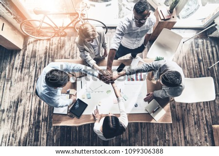 Victory!  Top view of young modern people in smart casual wear holding hands on top of one another in a symbol of unity while working in the creative office #1099306388