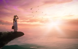 Victory vision concept: Silhouette traveler woman with birds flying on mountain sunset background
