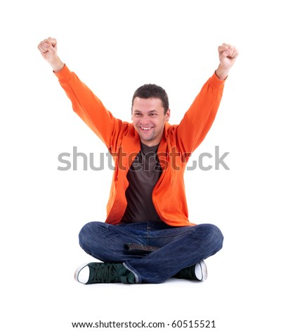 victory - young man in orange sweatshirt sitting on the floor with crossed legs and raised arms
