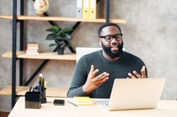 Video call. Attractive African-American guy is using laptop for video communication, a guy in glasses sits at the table in modern office, looking into webcam and talking online