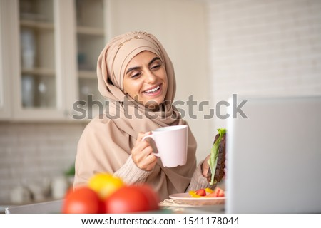 Video call. Beautiful Muslim girl having a video call while enjoying her healthy dinner