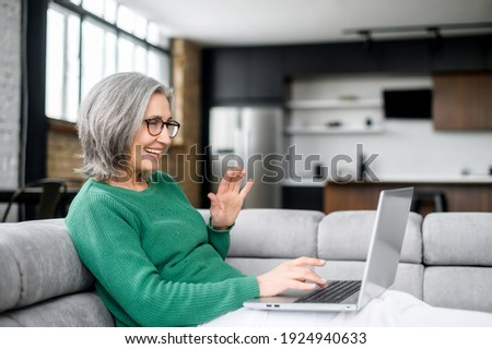 Video call concept, lovely elderly woman with nice wrinkles, narrow lips, smiling, chatting with family, using a laptop for video connection, remote meeting, say hi, glad to see, lying on the couch