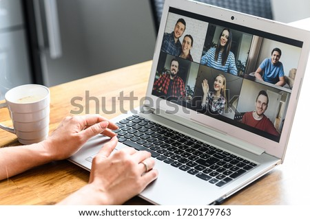 Photo of Video call. Icons of a group of people on laptop screen, app for video online communication. Female hands on the keyboard
