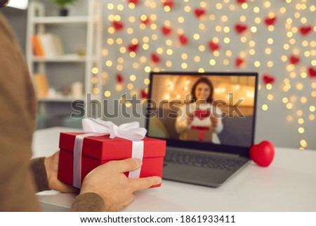 Video call on Saint Valentine's Day. Couple sending each other love and showing presents on virtual date. Closeup of man's hands holding gift box. Shimmering yellow lights, soft focus, selective focus Foto stock ©