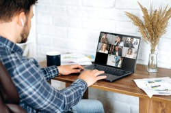 Video call. Online business meeting in video conference in the zoom app. A young attractive guy communicates with his colleagues on a video call using a laptop. Distant work at home