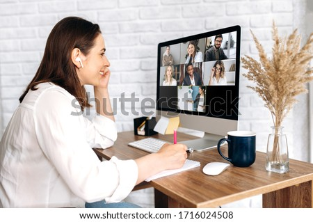 Video call. Remote work. A girl work from home. She communicate via video communication with colleagues using computer