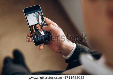 Video call. Remote work. Face of a smiling girl and african american guy on the screen of smartphone. A guy holds a phone in his hand and communicate via video communication with colleagues