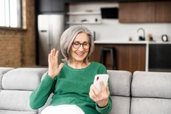 Video call, retired good-looking, grandmother speaks to her family or husband by video link sitting at home, close connection via phone, sincere elder woman, video connection, enjoys life in old age