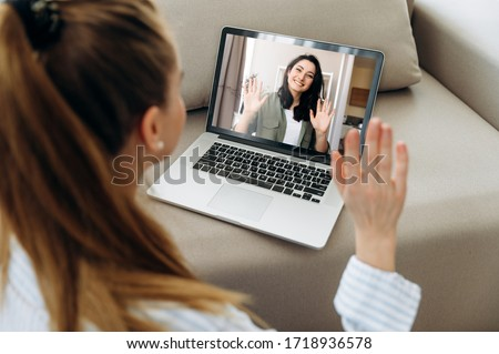 Video call. Two young attractive girls  communicate via video communication in zoom app using a laptop. Online meeting with friend