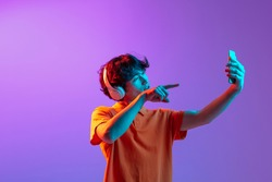 Video call. Young man talking on phone isolated over pink-purple background in neon light. Future, gadgets, digital technology concept. Human emotion, facial expressions. Copy space for ad, design.