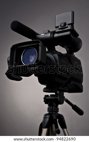Video camera and tripod on gray background