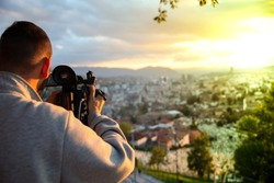 video camera, cameraman, sunset. The photographer records the sunset in the background of a beautiful city.-Image